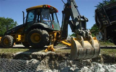 A large backhoe moving dirt